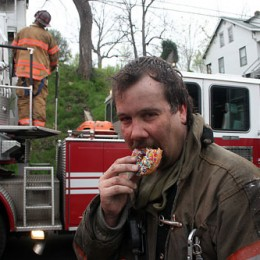 Captain Brown working the turntable on Ladder 1 while Lt. Randy Smith enjoys a doughnut. Photo courtesy of Mike Overacker