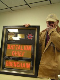 Retirement Dinner: Billy stands with his framed memorobilia